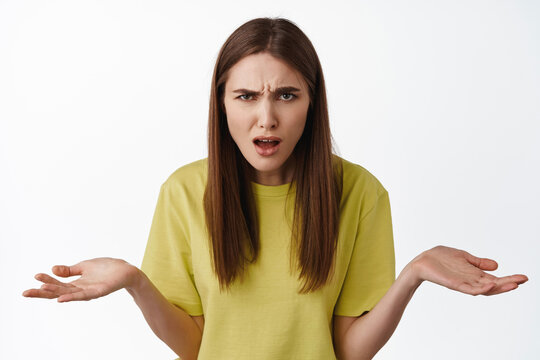 What big deal. Frustrated and confused woman shrugging, staring at camera annoyed, cant understand smth strange, wtf going on, standing against white background
