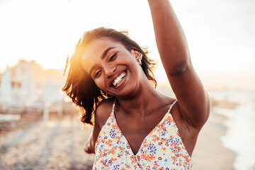 Fototapeta Cheerful woman smiling at the beach on sunset - Happy african female having fun walking by the sea - People and happiness concept  obraz