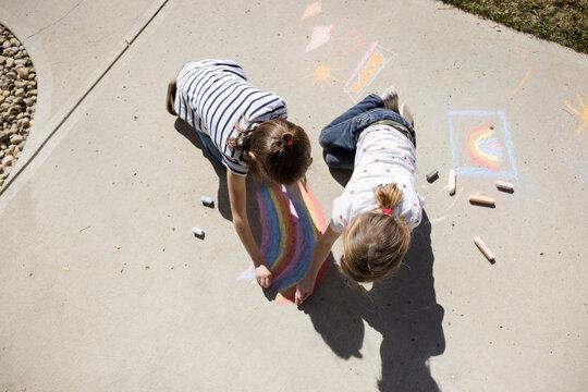 Overhead view of sisters drawing rainbows on walkway