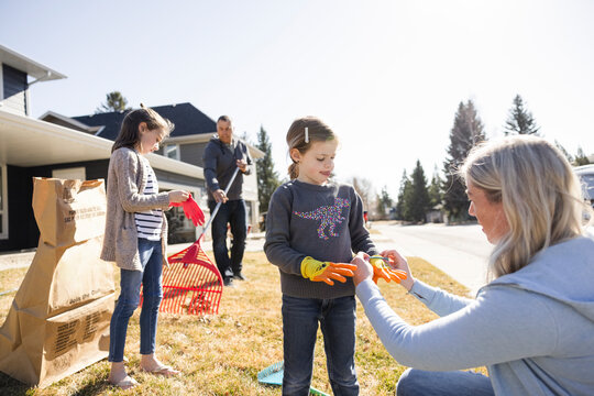 Mother helping daughter wear gloves in yard