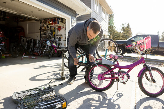 Man with digital tablet, fixing bicycle in driveway