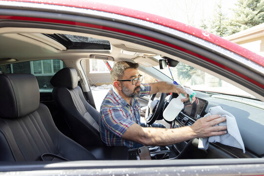 Bearded man wiping dashboard of car in driveway