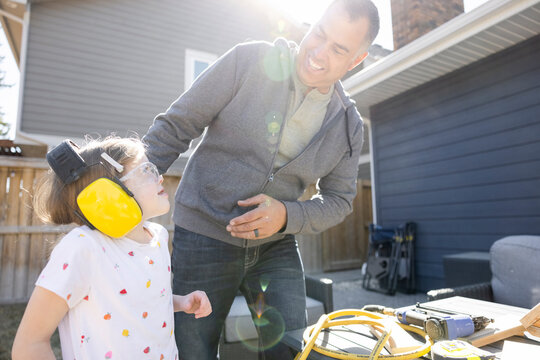 Cheerful father with daughter wearing headphones and safety glasses