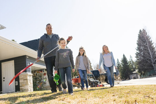 Cheerful family carrying tools to clean up yard