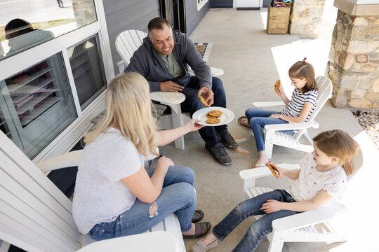 Family enjoying cookies at teatime on porch