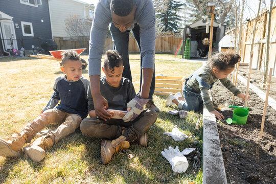 Father teaching son using phone in backyard