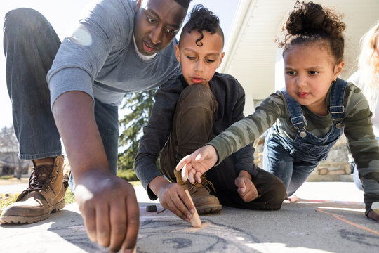 Father and children drawing on driveway
