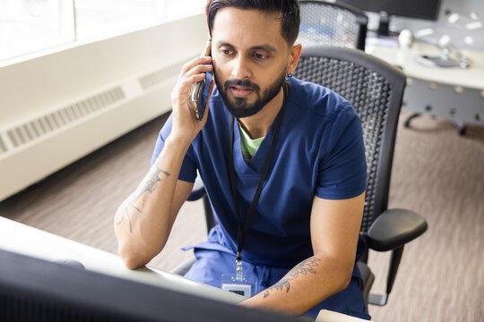 Male nurse talking on smart phone in clinic office