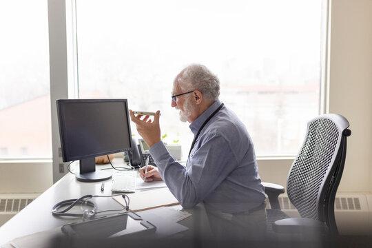 Senior male doctor talking on speaker phone at desk in clinic office