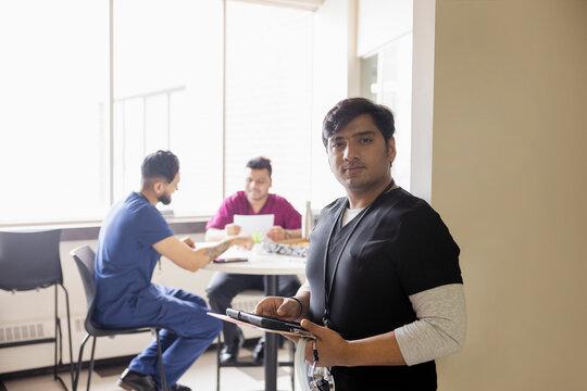 Portrait confident male nurse using digital tablet in clinic cafeteria
