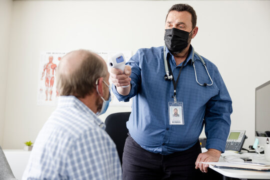 Male doctor in face mask using infrared thermometer on patient