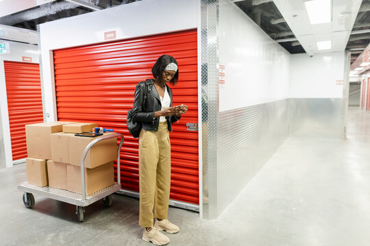 Woman with boxes using smart phone at storage facility locker