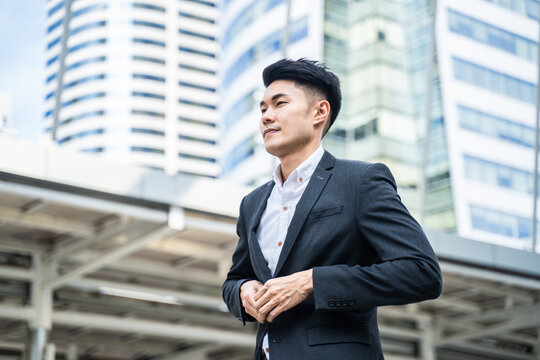 Asian young attractive office businessman worker stand outdoor in city
