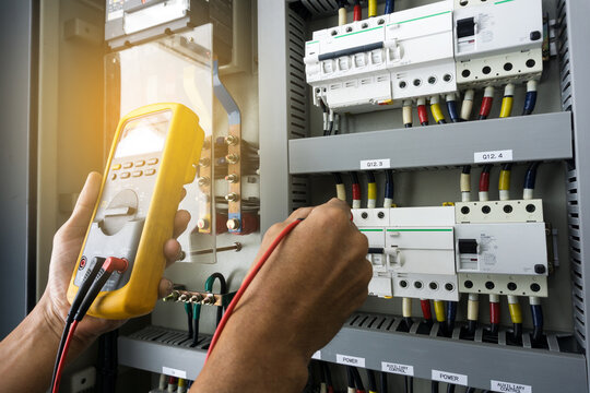 An electrician work tester measuring the voltage and current of electric power line in an electrical cabinet control.