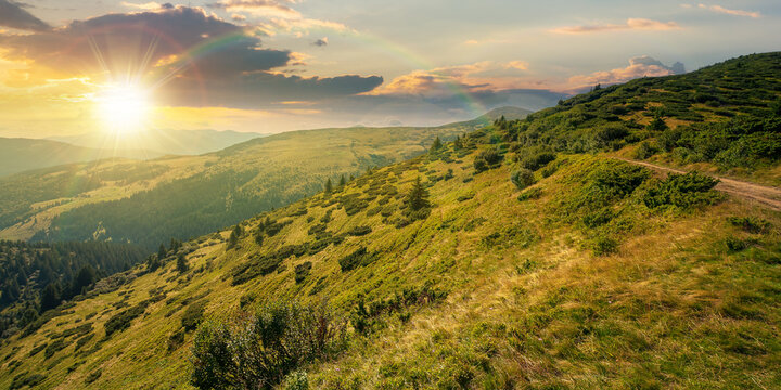 carpathian mountain landscape at sunset. beatiful scenery with green rolling hills in evening light beneath a dramatic sky with clouds in summer. explore backcountry concept