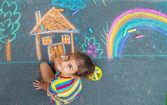 The child draws a house and a rainbow on the asphalt with chalk. Selective focus.