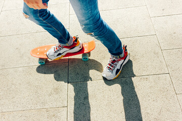 Young guy in ripped jeans standing with penny board in the park. summer activities skateboarding