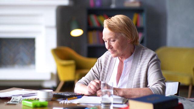 Sad senior woman sitting at able calculating medicine expenses