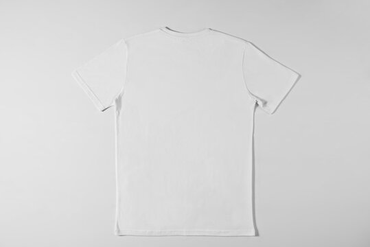 Simple white t-shirt lying on a white background