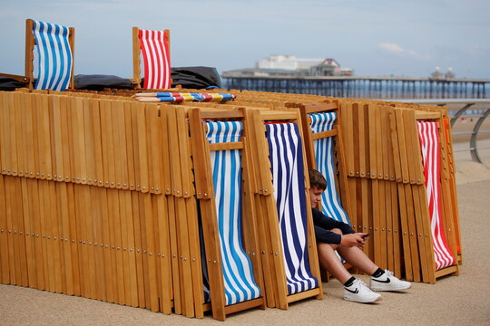 Deckchair attendant Luke Lee looks at his phone as he waits for customers as rental deckchairs returned to the seafront after a 10 year absence in Blackpool