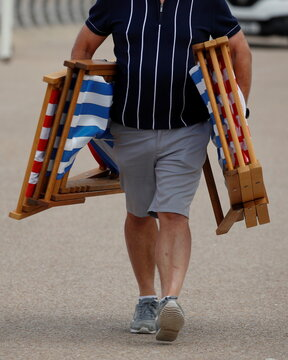 A man carries deckchairs along the promenade as rental deckchairs returned to the seafront after a 10 year absence in Blackpool