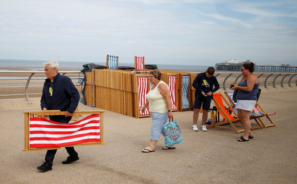A deckchair attendant carries a chair for a customer as rental deckchairs returned to the seafront after a 10 year absence in Blackpool
