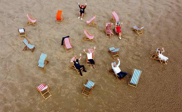People pose for a photograph as they sit in deckchairs on the beach as rental deckchairs returned to the seafront after a 10 year absence in Blackpool