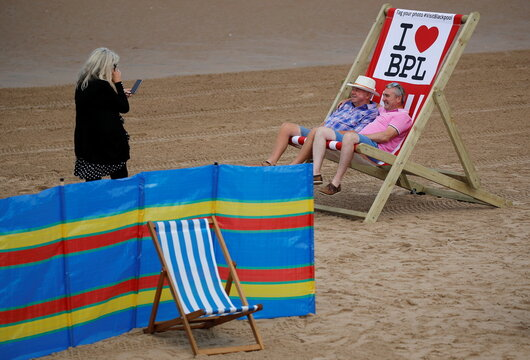 People pose for a photograph in a giant deckchair as rental deckchairs returned to the seafront after a 10 year absence in Blackpool