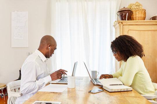 Business Mann und Partnerin arbeiten am Laptop im Homeoffice