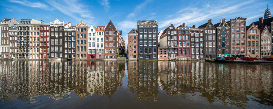 Panoramic view of traditional houses along the Damrak canal in Amsterdam, Netherlands