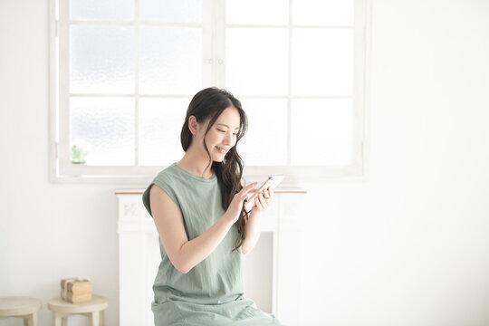 スマホでタップする見る美しい日本人女性の広角真ん中2 コピースペースあり