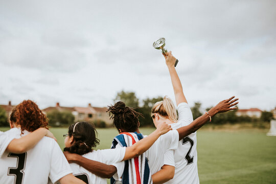 Female football players taking a winning cup back home