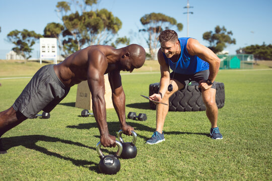 African american muscular man exercising outdoors with kettle bells and fitness instructor