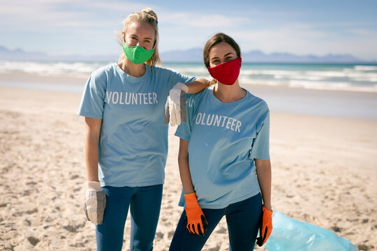 Two diverse women wearing volunteer t shirts and face masks picking up rubbish from beach
