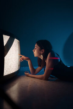Woman lying down near old television in darkness