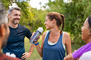 Thirsty mature woman drinking water after workout