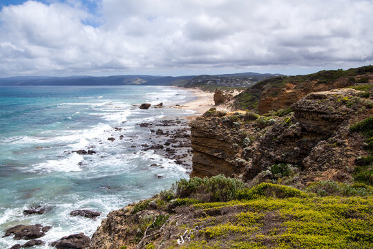 A large panorama view over the rocky coastline of the Australian coast near the Great Ocean Road. Giant waves break on the rocky shore. Steep cliffs break over to the sandy beach. Cloudy sky.