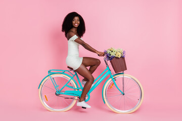 Full size profile side photo of young afro girl happy positive smile ride bicycle isolated over pink color background Wall mural