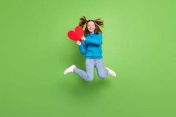 Full size photo of happy young girl jump up hold heart wear jeans sweater hoodie fly hair isolated on green color background Wall mural