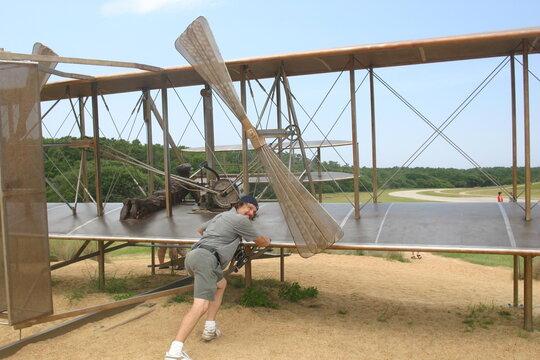 Man at Kill Devil Hills North Carolina Kitty Hawk Pushing a Statue of the Wright Flyer