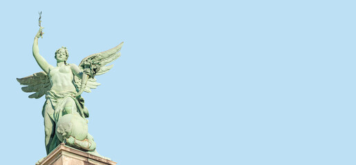 Banner with top roof statue of sensual Renaissance Era angel with wings in front of blue sky with copy space in Vienna, Austria, with blue sky solid background.