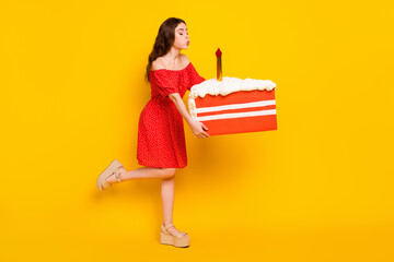 Full length profile side photo of young girl happy positive smile hold cake blow candle isolated over yellow color background Wall mural