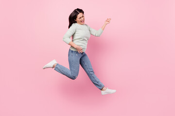 Full length photo of funky cheerful young woman jump up play imagine guitar isolated on pink color background Wall mural
