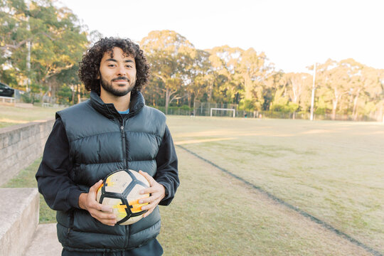 Close up shot of a smiling young man with curly hair standing on the field with a soccer ball