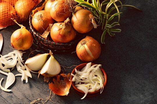 Cebollas y rodajas sobre tabla de cortar de madera y cesto de mimbre. Fondo de alimentos saludables.