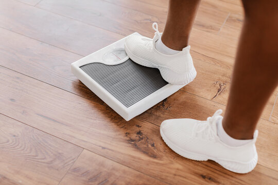Closeup of African Woman Standing On Scales. Slimming Concept