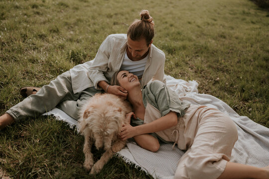 young couple and a dog having a picnic