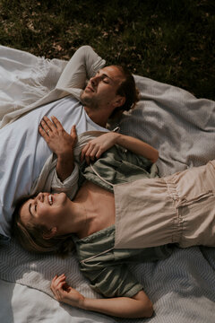 young happy couple is lying on a picnic blanket