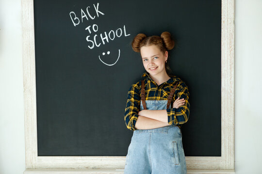 Happy smiling girl. Child at the blackboard. Girl indoor classroom with chalkboard on background. We return to school. High quality photo