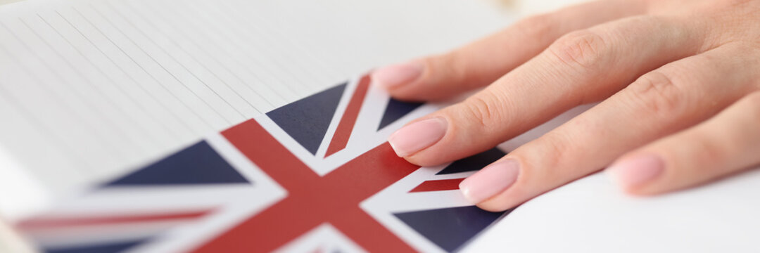 Woman holding diary with bookmark in form of flag of england closeup